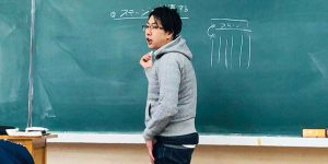黒板の前にたつ柴田
